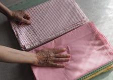 Den äldre kvinnan räcker att vika upp kläderna, slut arkivbilder