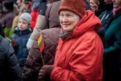 Den äldre kvinnan rymmer den litauiska flaggan Royaltyfria Foton
