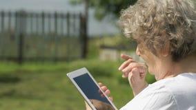 Den äldre kvinnan rymmer en datorminnestavla utomhus lager videofilmer