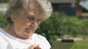 Den äldre kvinnan rymmer en datorminnestavla utomhus arkivfilmer