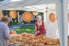 Den äldre kvinnan säljer saker från pilfilialer royaltyfri foto