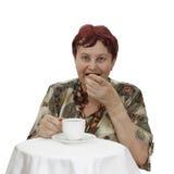 Den äldre kvinnan sitter på tetabellen Royaltyfri Bild