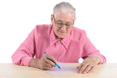 Den äldre kvinnan skriver dokumentet Arkivfoton