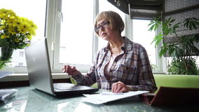 Den äldre kvinnan som använder internetbankrörelsen i hem lager videofilmer