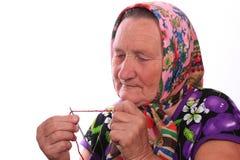 Den äldre kvinnan som sätter in tråden i visaren Royaltyfri Bild