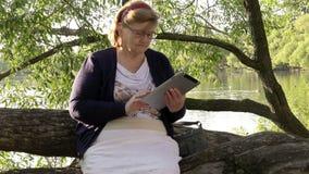 Den äldre kvinnan som sammanträde på ett träd i en stad parkerar, överför mejl, genom att använda informationsteknikminnestavlan lager videofilmer