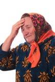 Den äldre kvinnan som trycker på med handen till huvudet Royaltyfri Foto