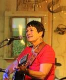 Den äldre kvinnan spelar gitarren och sjunger Arkivbild