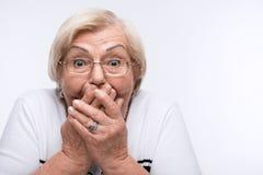 Den äldre kvinnan stänger hennes mun, gå i ax och synar med Royaltyfria Foton