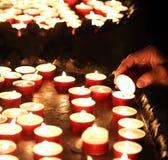 Den äldre kvinnan tänder en stearinljus för att be under mass Royaltyfri Bild