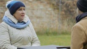 Den äldre kvinnan talar med mansammanträde i det friakafé arkivfilmer