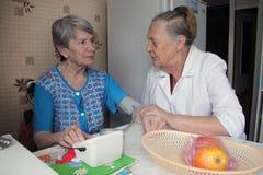 Den äldre kvinnan tröstar hennes vän royaltyfria foton