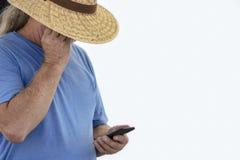 Den äldre långa gråa haired mannen i bred brättesugrörhatt och utslagsplatsskjortan skuggar hans ögon för att se mobiltelefonen - arkivbilder