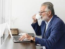 Den äldre mannen använder datorbärbara datorn arkivbilder