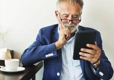 Den äldre mannen använder den digitala minnestavlan arkivfoto