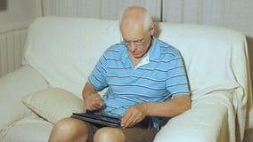 Den äldre mannen använder minnestavlan stock video
