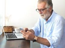 Den äldre mannen använder mobiltelefonen royaltyfri bild