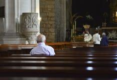 den äldre mannen ber i en kyrka Arkivbild