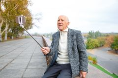 Den äldre mannen gör selfie på en mobiltelefon med en monopod Utomhus på gatan fotografering för bildbyråer