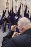 Den äldre mannen gjorde ren deras revor som var upphetsade, når han har hållit ögonen på helig vecka Royaltyfri Foto