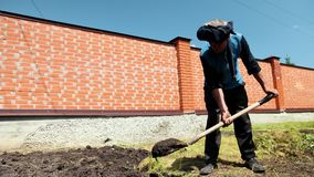 Den äldre mannen gräver en skyffel jordningen nära ett högt staket i soligt väder arkivfilmer