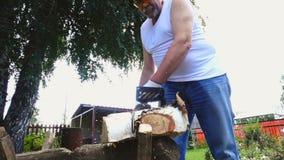 Den äldre mannen i skyddande exponeringsglas som sågar björken, loggar stock video