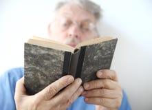 Den äldre mannen läser boken Royaltyfri Bild