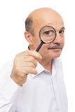 Den äldre mannen ser något till och med ett förstoringsglas Royaltyfri Foto