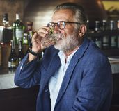 Den äldre mannen sitter i en bar royaltyfri foto