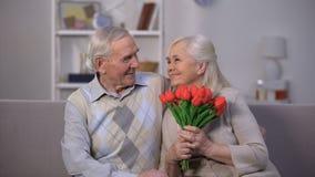 Den äldre mannen som kramar den lyckliga kvinnan med gruppen av tulpan, framlägger från älskling stock video