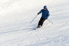 Den äldre mannen som ner skidar, skidar lutningen Arkivfoto