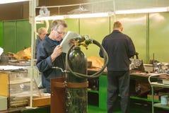 Den äldre mekanikern läser teckningen shoppar in Royaltyfri Bild
