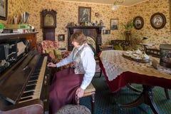 Den äldre pensionerade kvinnan spelar pianot på hennes hem royaltyfria bilder