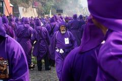Den äldre purpurfärgade bestulna mannen along gol av lilor klädde män på processionen av San Bartolome de Becerra i 1a Avenida Arkivfoto