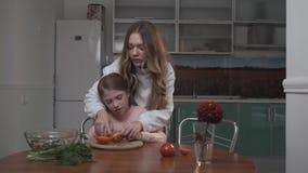 Den äldre systern undervisar mer ung syster att klippa tomater för sallad Två systrar som reser upp grönsaksallad, medan sitta på arkivfilmer