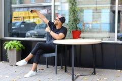 Den älskvärda arabiska grabben gör selfie och att lyfta armen och sitter i stol, s fotografering för bildbyråer