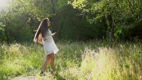 Den älskvärda brunettflickan rotera bärande den omkring vita klänningen i parkerar stock video