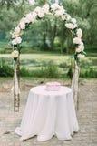 Den älskvärda dekorerade bågen med vita blommor bak tabellen med mycket små rosa färger boxas på den Royaltyfri Fotografi