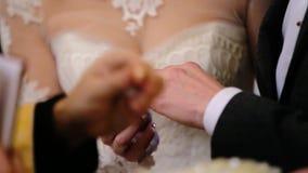 Den älskvärda härliga bruden som bär den trendiga vita bröllopsklänningen, satte den guld- cirkeln på ett finger av en ung brudgu stock video