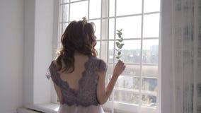Den älskvärda kvinnan är vaknade och stå för fönster Flickaöppningsgardiner som möter soluppgång lager videofilmer