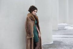 Glamour. Outwear den fundersama kvinnan för skönhet över vitväggen i ull att drömma royaltyfri bild