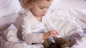 Den älskvärda lilla flickan kysser hennes bästa vän älskade nallebjörn som leksaken sitter i vit säng stock video