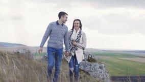Den älskvärda mannen kommer till hennes kvinna, omfamnar och kysser henne på naturen 4K stock video