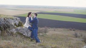 Den älskvärda mannen omfamnar och kysser hans kvinna på naturen 4K lager videofilmer