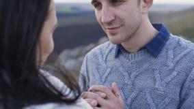 Den älskvärda mannen värme och kysser handen för kvinna` s i blåsig dag 4K lager videofilmer