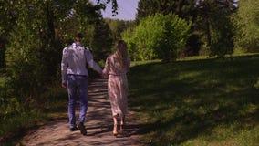 Den älskvärda paromfamningen går på en vandringsled i en trädgård Älskvärda par går i det lilla trät Barnpar på skogen arkivfilmer