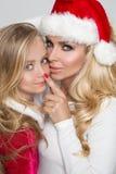 Den älskvärda sexiga blonda modern med en dotter för behandla som ett barnflicka klädde som Santa Claus Arkivbild