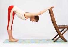 Den älskvärda sportiga kvinnan som gör sträckning, övar Arkivbild