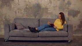 Den älskvärda trötta flickan med att ta för bok ta sig en tupplur på soffan stock video