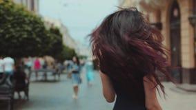 Den älskvärda unga brunettkvinnan i svarta tillfälliga kläder går ner gatan för den centrala staden, vänder och ler rakt till lager videofilmer